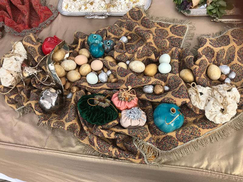 decorated eggs, nuts, ceramic pomegranates on metallic fringe