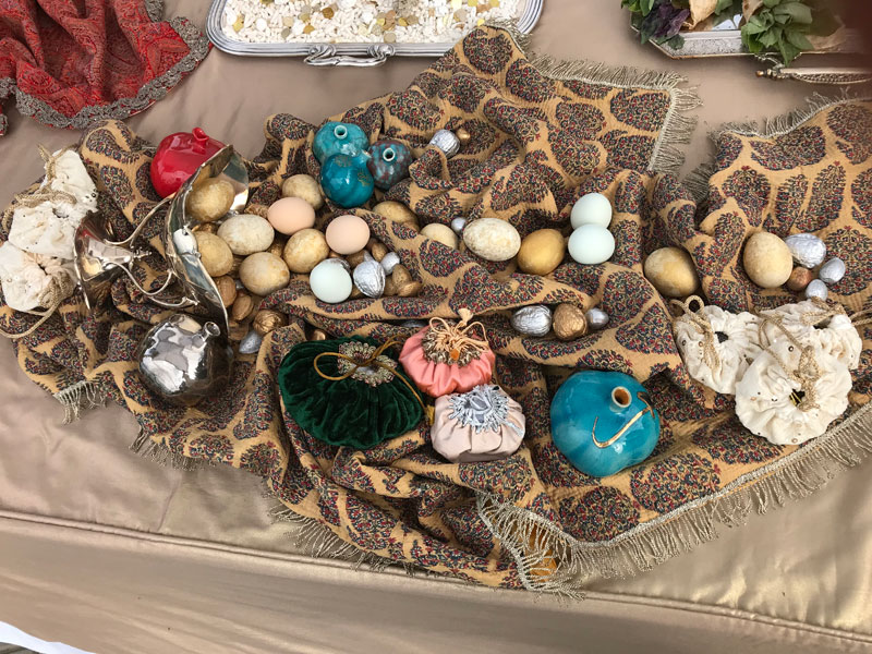 decorated eggs, nuts, ceramic pomegranates on metallic fringe