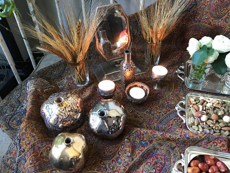 sofreh of mirror, candles, bunches of wheat and ceramic pomegranates