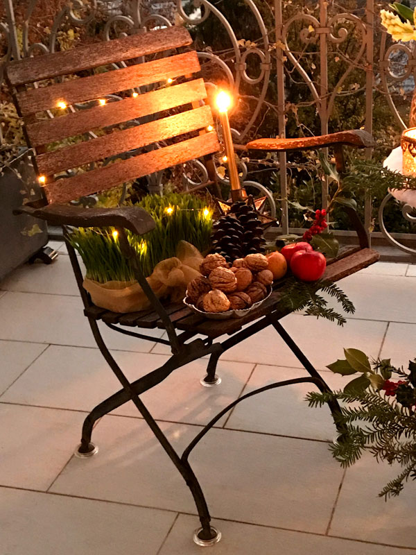 garden chairs featuring fresh sabzeh illuminated by Christmas tree lights