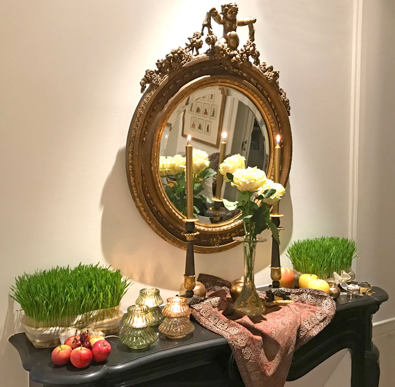 ornate mirror over a black marble mantelpiece