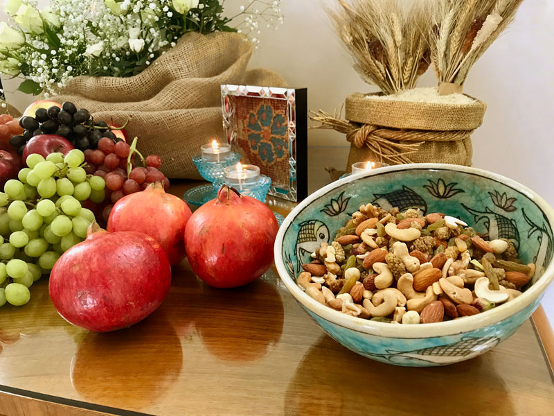 shiny pomegranates and container of mixed dried fruit and nuts