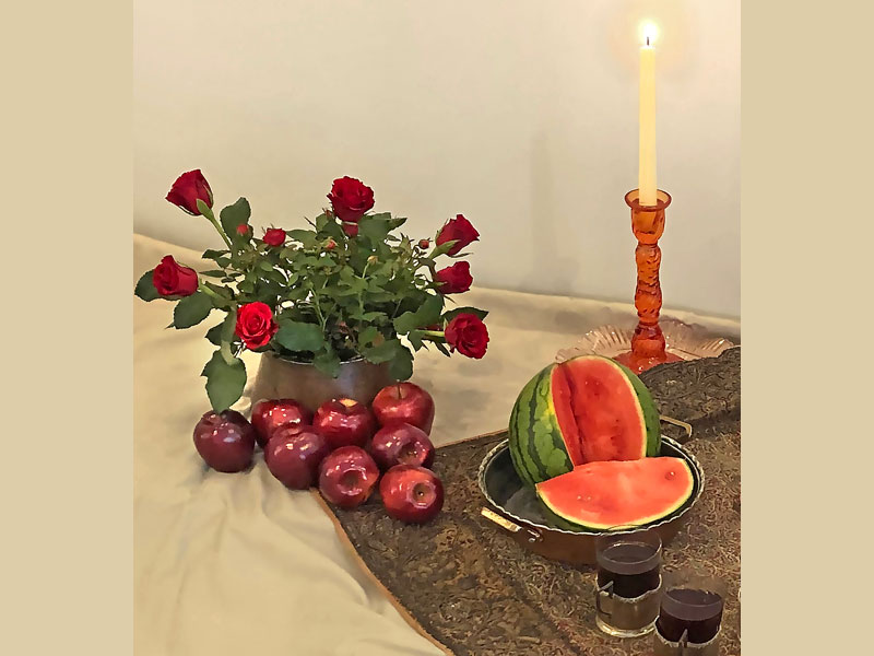 deep-red rose plant and Freedom cut roses, arranged in a traditional copper vessel