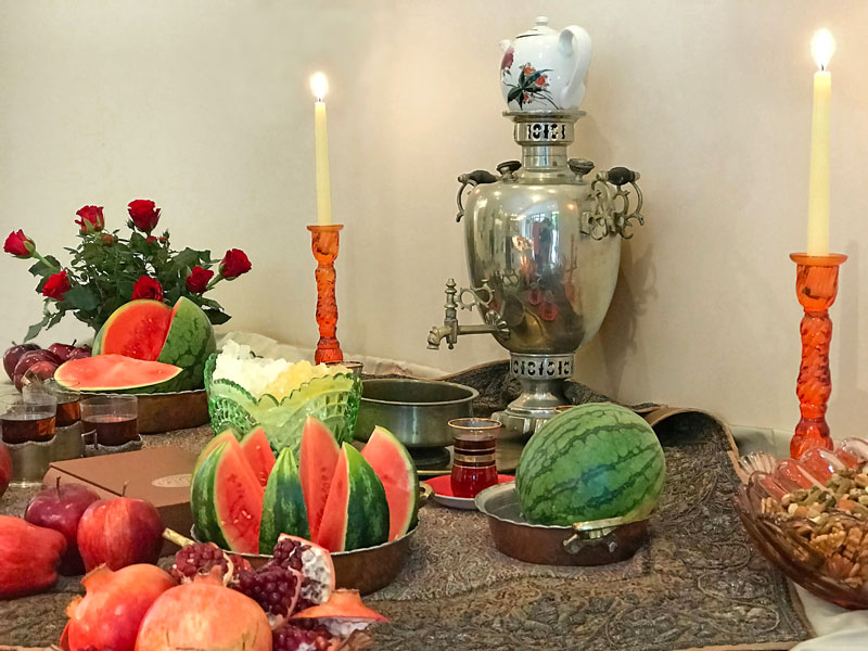 tea paraphernalia, candleholders, crystal sugar, whole and cut watermelons, pomegranates and apples