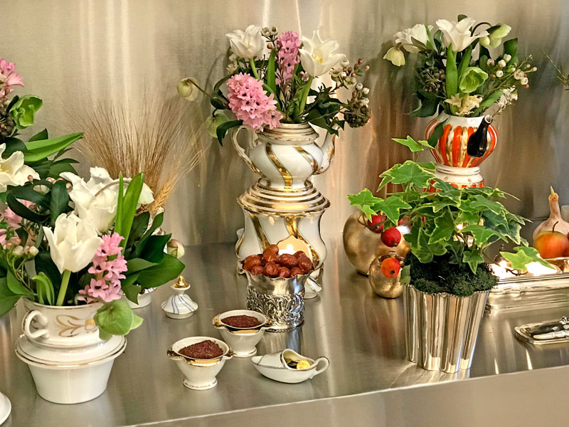 teapots hold bouquets of spring flowers