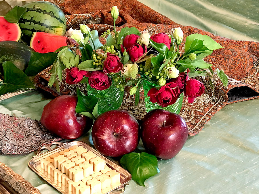 red bouquet and apples on termeh