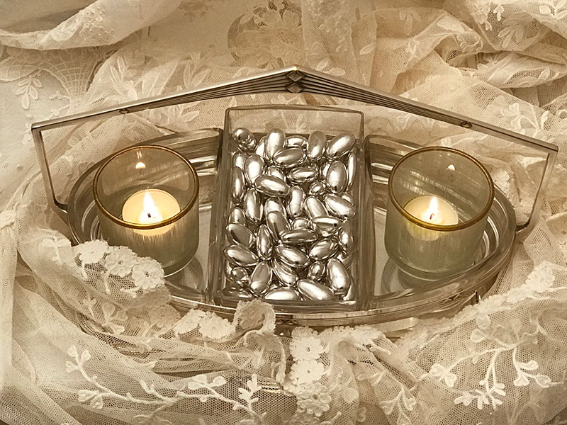 silver almonds and candles on lace