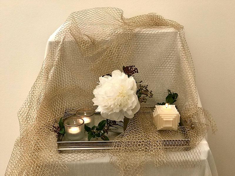 white peony, sprigs of Viburnum tinus and candle
