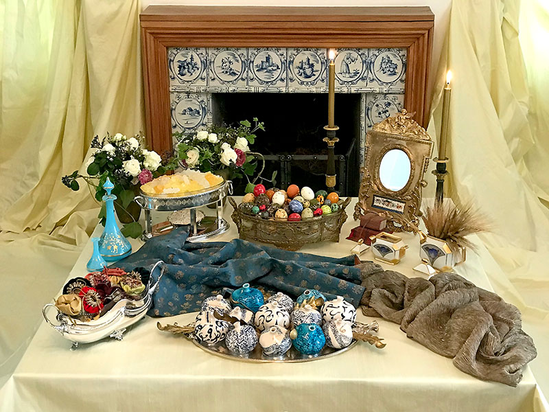 sofreh with blue and gold, candles, eggs, pomegranates