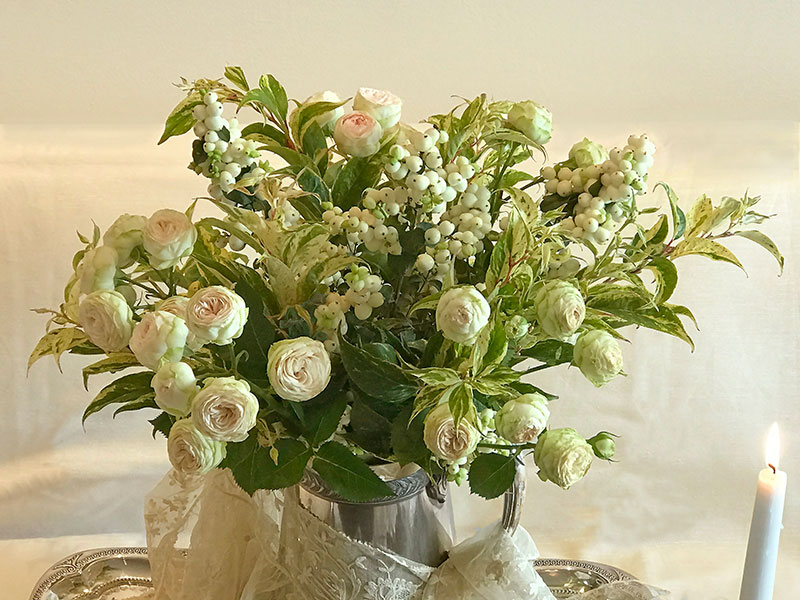 spray roses, snowberries, and variegated foliage